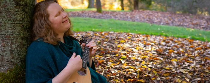 Redheaded woman playing the ukulele, sitting against a tree